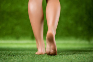 His bare feet beautiful woman close up are on a grass
